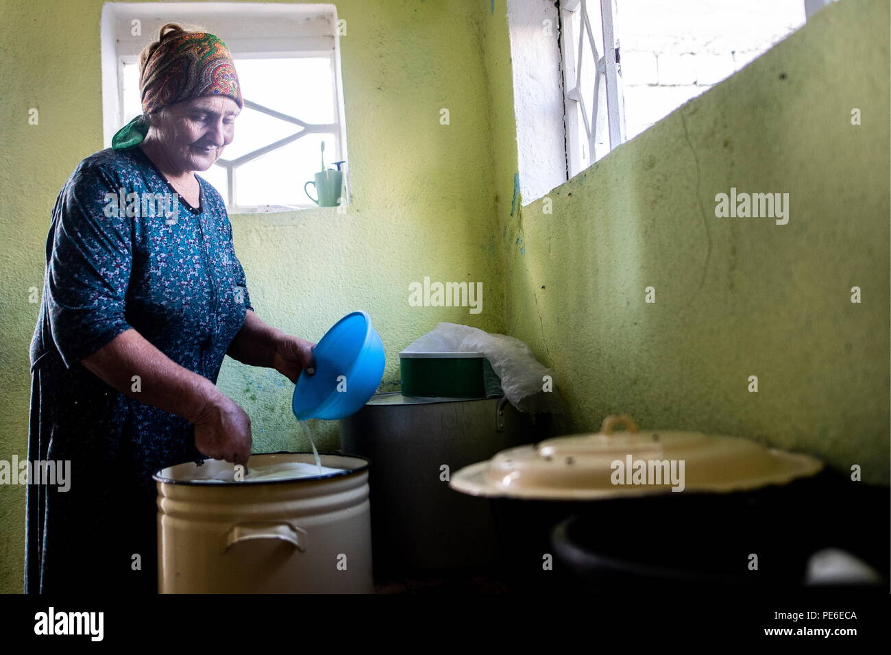 South Ossetia. 11th Aug, 2018. SOUTH OSSETIA - AUGUST 11, 2018: Margarita Madzigova, 63, makes home cheese in the village of Khetagurovo, Tskhinvali District, South Ossetia; Margarita and her husband Alikhan have been running a farm since their house was restored after the 2008 South Ossetian-Georgian military conflict. Sergei Bobylev/TASS Credit: ITAR-TASS News Agency/Alamy Live News - Stock Image