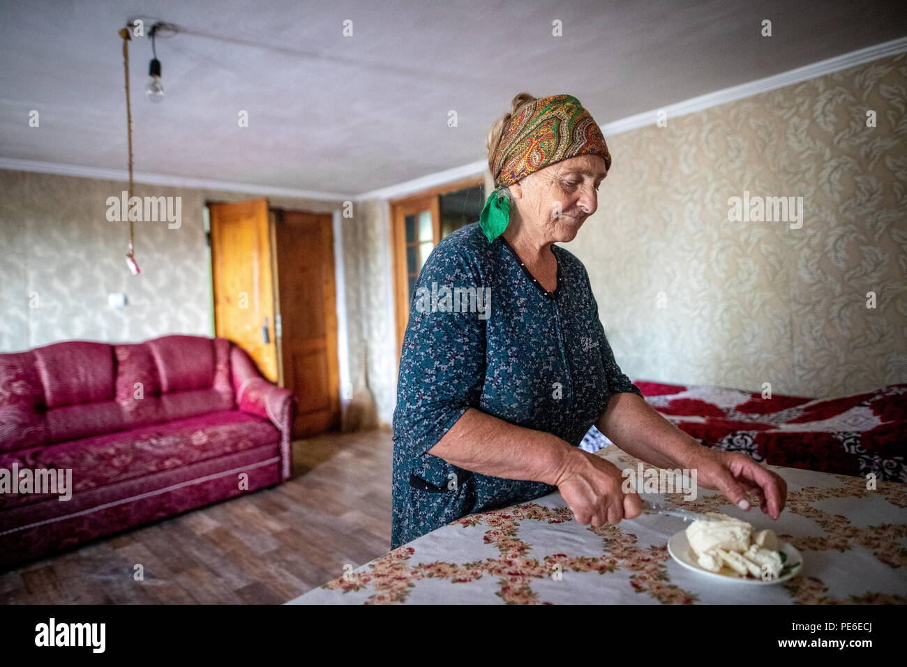 South Ossetia. 11th Aug, 2018. SOUTH OSSETIA - AUGUST 11, 2018: Margarita Madzigova, 63, cuts home cheese in the village of Khetagurovo, Tskhinvali District, South Ossetia; Margarita and her husband Alikhan have been running a farm since their house was restored after the 2008 South Ossetian-Georgian military conflict. Sergei Bobylev/TASS Credit: ITAR-TASS News Agency/Alamy Live News - Stock Image