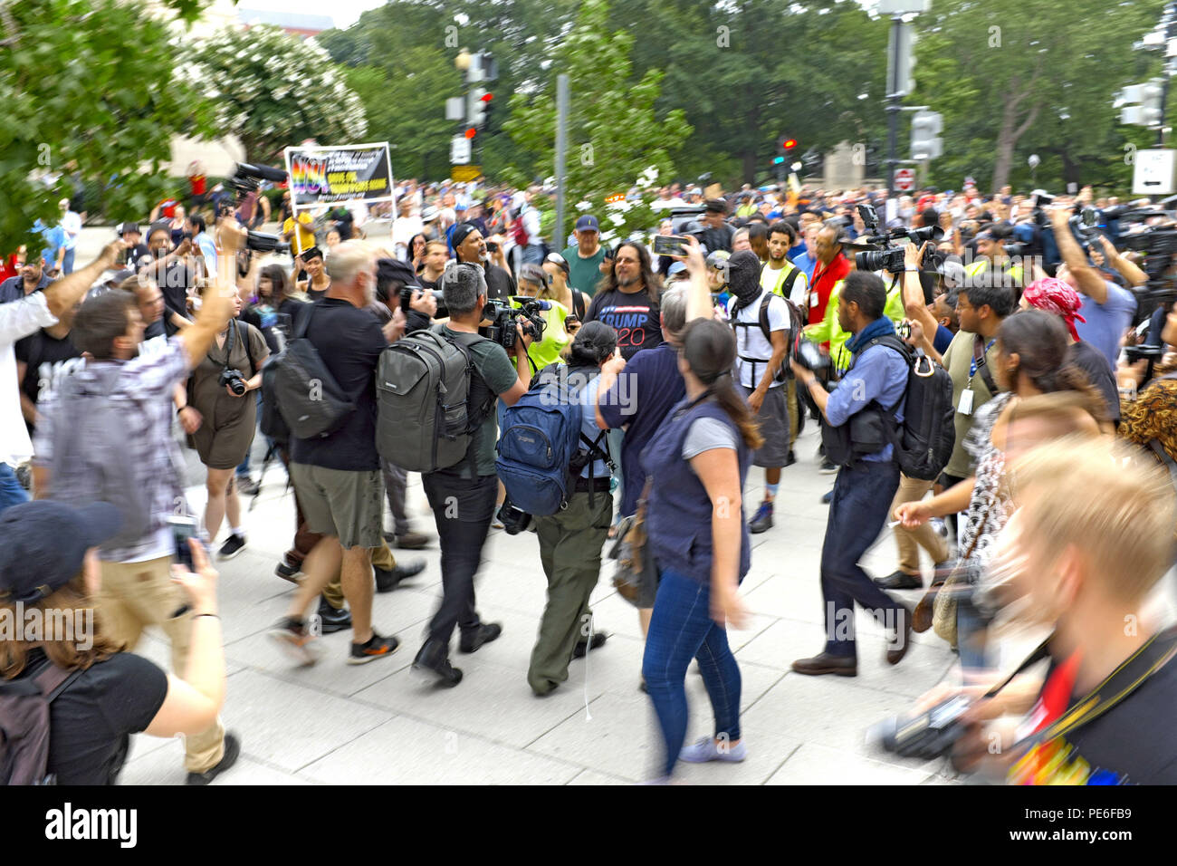 Washington D.C., USA. 12th August, 2018.  An alt-right supporter leaves the 'Unite the Right 2' rally in Lafayette Park to a crowd of counterprotesters and photographers.  Dressed in a Trump 2020 t-shirt, the man is attempting to leave the rally while people are shouting at him.  The photo was taken before he sought police protection nearby.  Credit: Mark Kanning/Alamy Live News. Stock Photo