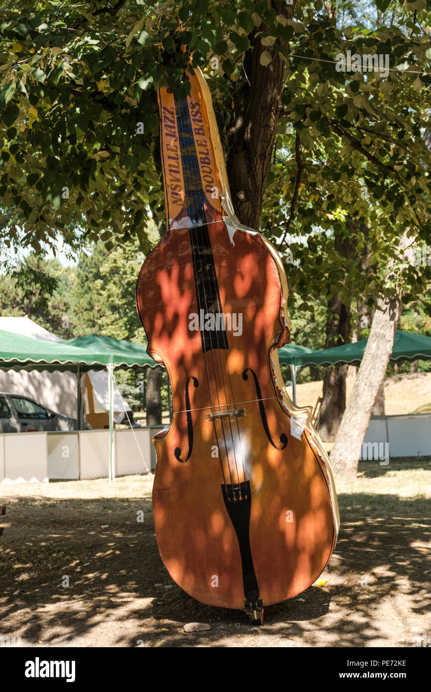 Nis, Serbia - August 12, 2018: Big model of double bass in nature on jazz festival in city of Nis, Serbia. Jazz music concept - Stock Image