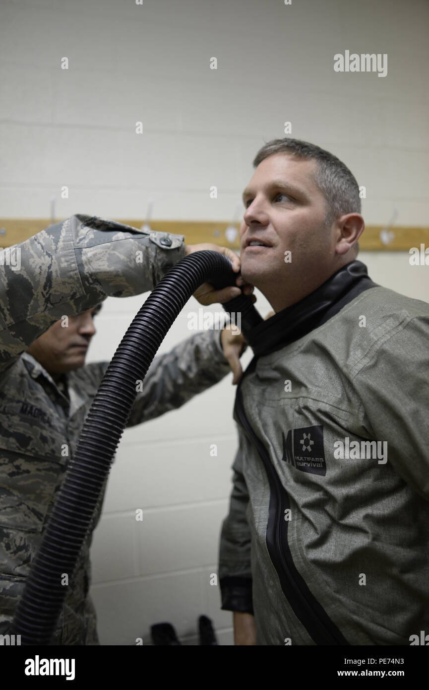 United States Air National Guard member, Tech. Sgt. Ruben Madrigal, 144th Fighter Wing Aircrew Flight Equipment, removes any extra air from the cold weather outer garment flight suit as Lt. Col. Robert Swertfager, 194th Fighter Squadron fighter pilot, waits patiently in Exercise Vigilant Shield 16 at 5 Wing Goose Bay, Canada, Oct. 19, 2015. From Oct. 15-26, 2015,, approximately 700 members from the Canadian Armed Forces, the United States Air Force, United States Navy and the United States Air National Guard are deploying to Iqaluit, Nunavut, and 5 Wing Goose Bay, Newfoundland, Labrador for Ex Stock Photo