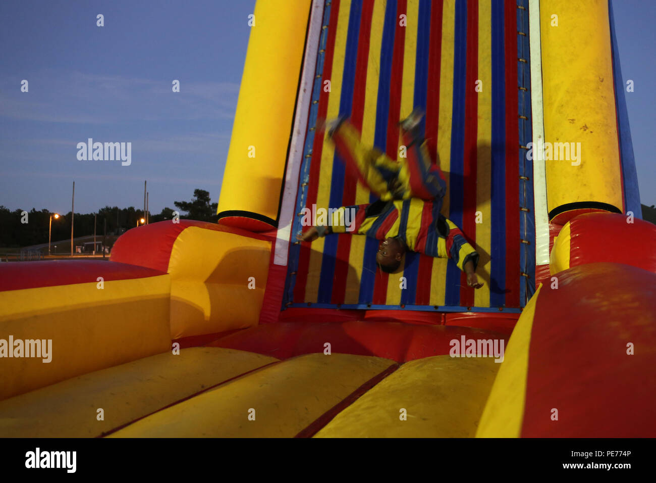 Lance Cpl. Daijon Reason flips through the air before sticking to an inflatable Velcro sticky wall while wearing a Velcro suit during the Fall Family Festival hosted by Marine Air Control Squadron 2 at Marine Corps Air Station Cherry Point, N.C., Oct. 22, 2015. More than 100 Marines, Sailors and family members gathered to kick off the fall season with a chili cook-off and costume contest as well as games, a movie and a bonfire. Reason is a tactical air defense controller with MACS-2. (U.S. Marine Corps photo by Cpl. N.W. Huertas/Released) - Stock Image