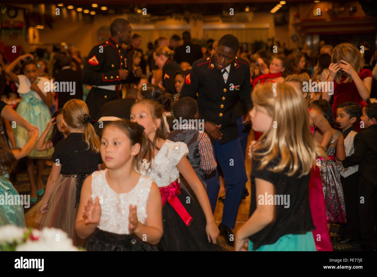 Marines and children dance during the Mini-Marine Corps Ball in the Club Iwakuni ballroom at Marine Corps Air Station Iwakuni, Japan, Oct. 23, 2015. Children dressed up, danced, ate and experienced a Marine Corps tradition during the event. The children, ranging from 5 to 12 years old, were afforded the opportunity to learn about the traditions of the Marine Corps Ball including, the cake cutting ceremony where the oldest and youngest Marine present are presented the first slice of cake. (U.S. Marine Corps photo by Pfc. Aaron Henson/Released) - Stock Image