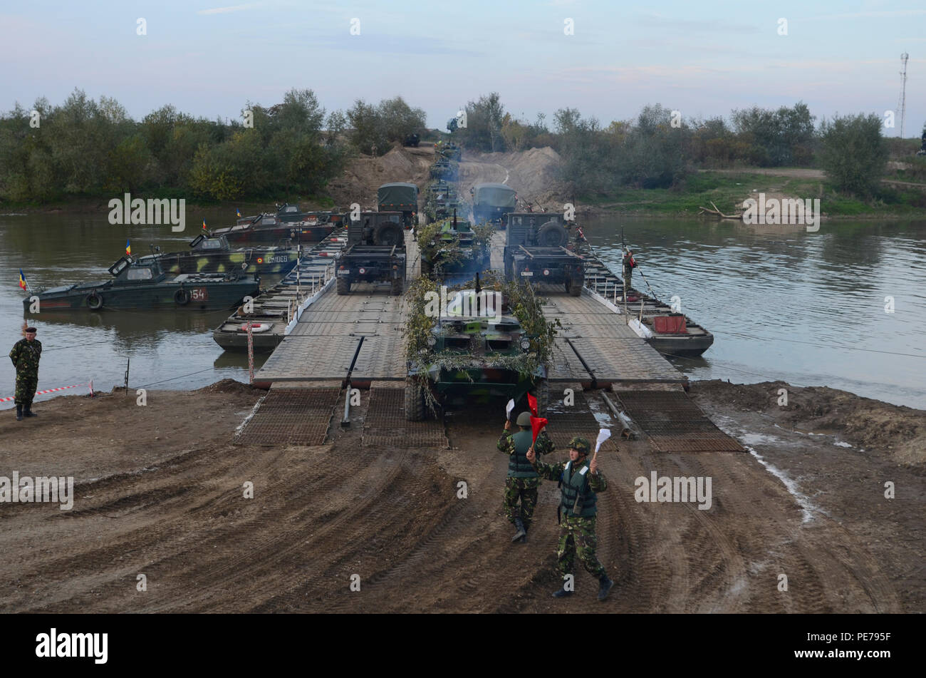 Romanian Soldiers direct traffic as U.S. military vehicles cross the three-lane floating bridge during Exercise Dragoon Crossing – Romania near Arad, Romania, Oct. 24-26, 2015. Dragoon Crossing – Romania is a strengthening of NATO's persistent presence in the region in support of Operation Atlantic Resolve.  (U.S. Army photo by Staff Sgt. Steven M. Colvin/10th Press Camp Headquarters) - Stock Image