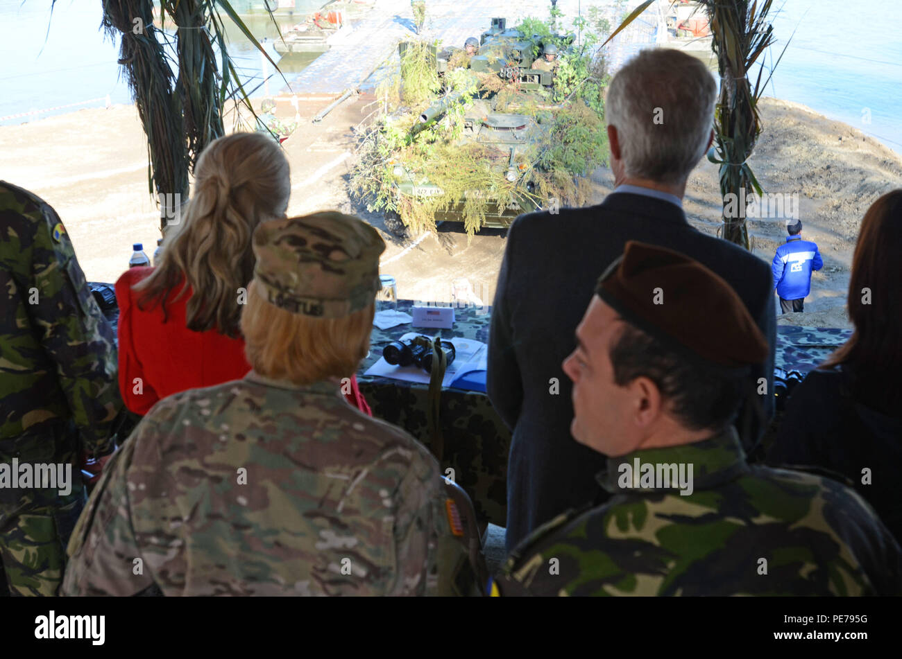 U.S. and Romanian Soldiers and key leaders watch as U.S. military vehicles cross the three-lane floating bridge during Exercise Dragoon Crossing – Romania near Arad, Romania, Oct. 24-26, 2015. Dragoon Crossing – Romania is a strengthening of NATO's persistent presence in the region in support of Operation Atlantic Resolve.  (U.S. Army photo by Staff Sgt. Steven M. Colvin/10th Press Camp Headquarters) - Stock Image