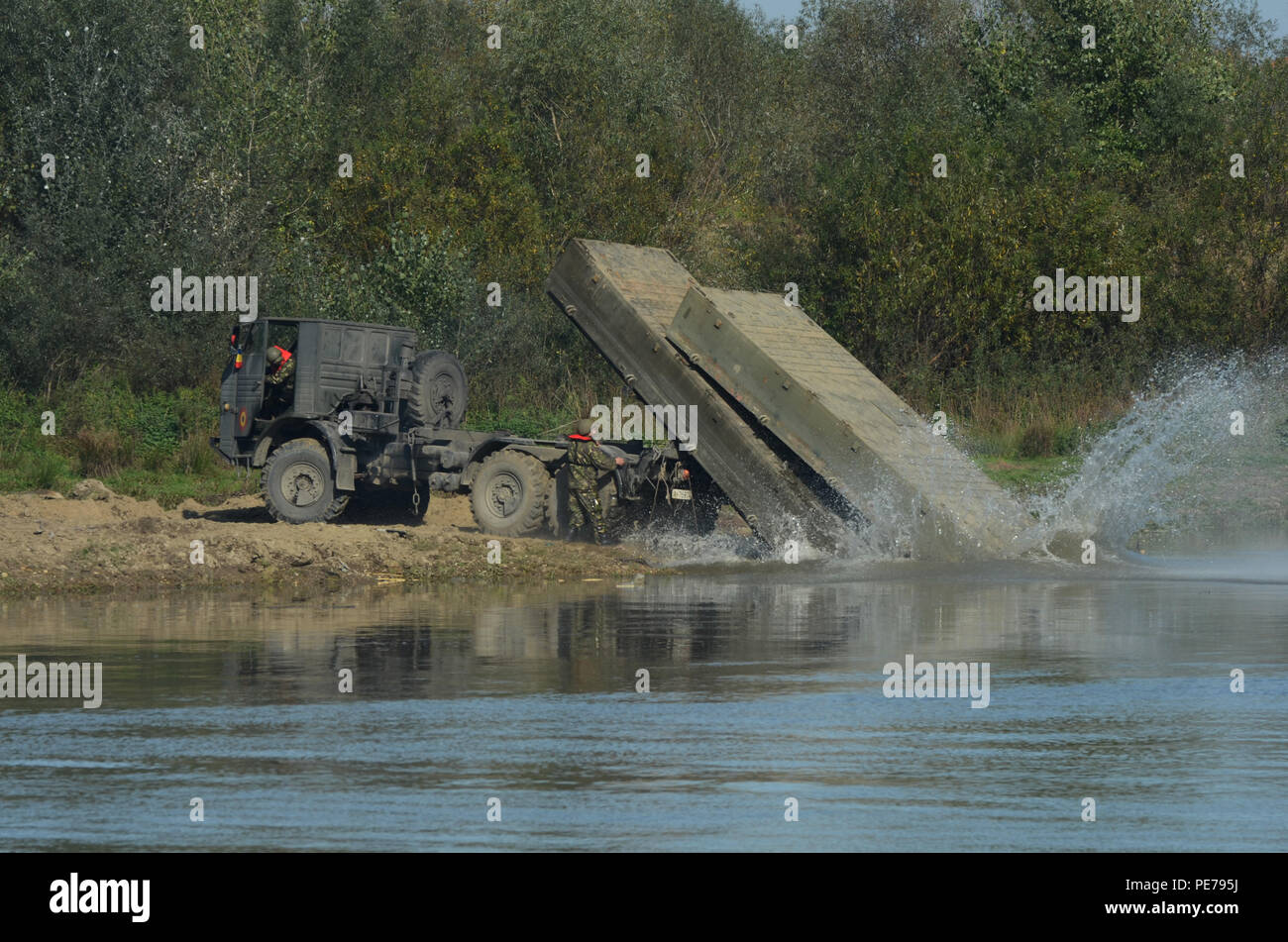 Romanian Soldiers demonstrate how they unload pieces of the floating bridge into the Mures River during Exercise Dragoon Crossing – Romania near Arad, Romania, Oct. 24-26, 2015. Dragoon Crossing – Romania is a strengthening of NATO's persistent presence in the region in support of Operation Atlantic Resolve.  (U.S. Army photo by Staff Sgt. Steven M. Colvin/10th Press Camp Headquarters) - Stock Image