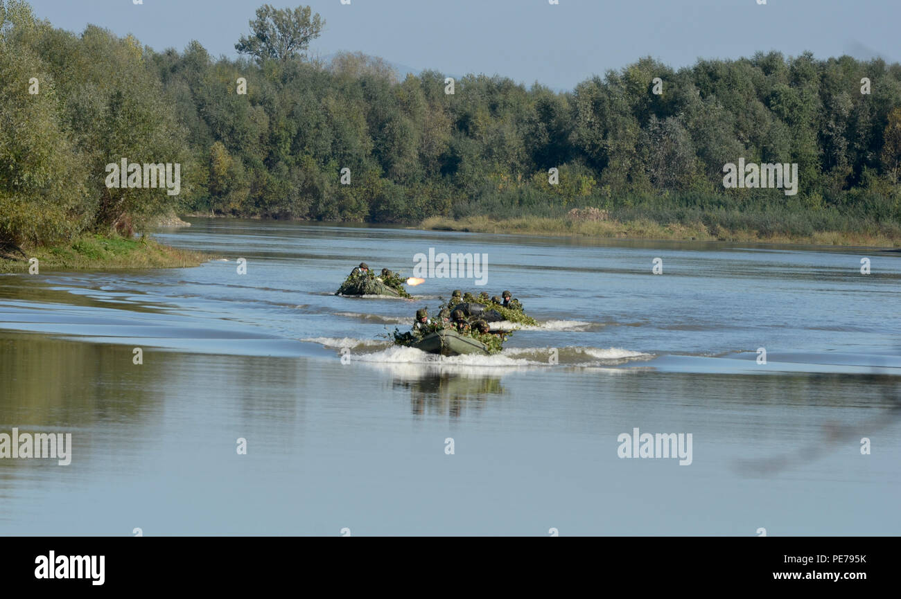 Romanian Soldiers suppress enemy fire while crossing the Mures River on  camouflaged rafts during Exercise Dragoon Crossing – Romania, Oct. 24-26, 2015. Dragoon Crossing – Romania is a strengthening of NATO's persistent presence in the region in support of Operation Atlantic Resolve.  (U.S. Army photo by Staff Sgt. Steven M. Colvin/10th Press Camp Headquarters) - Stock Image