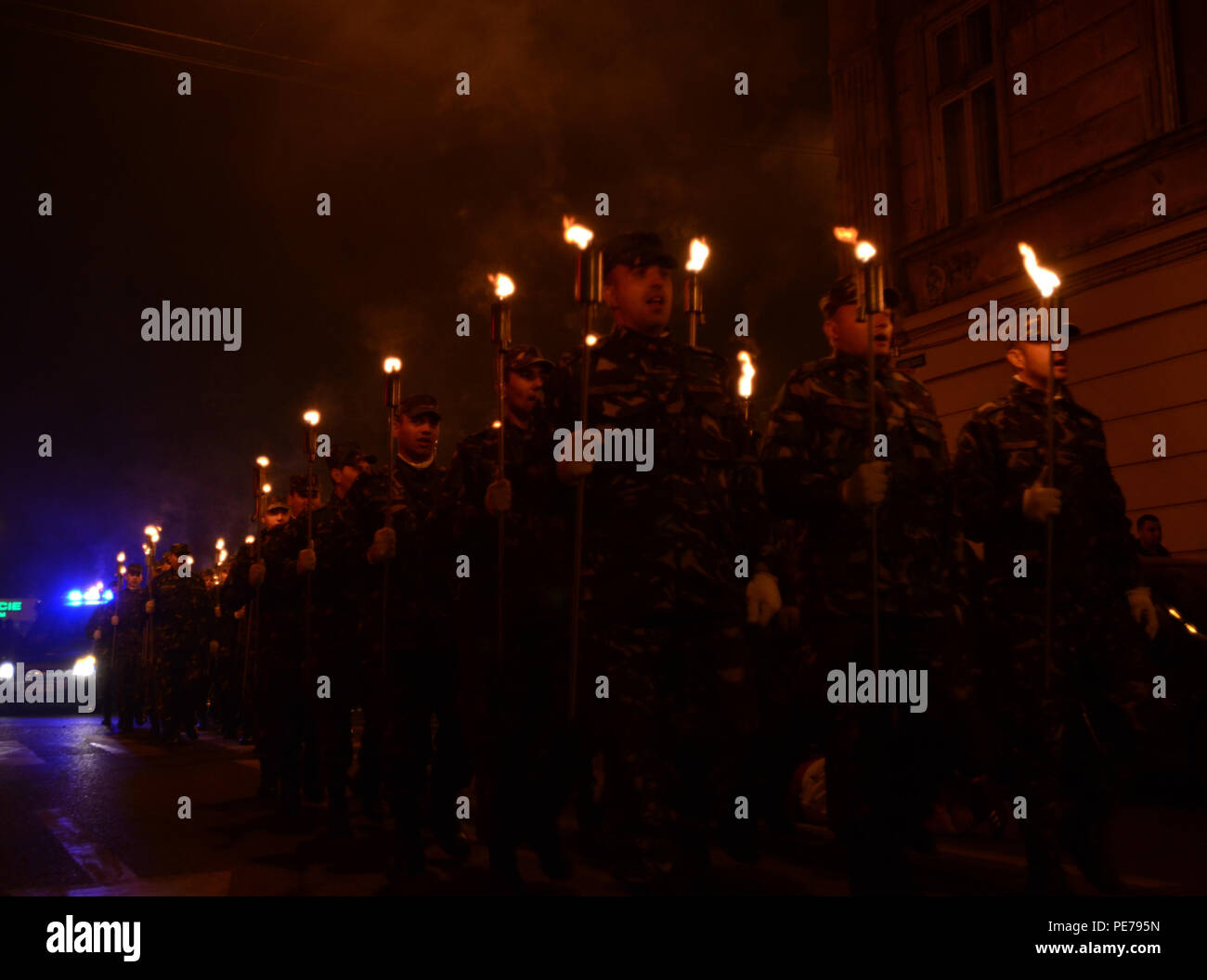 """Romanian Soldiers march through the streets of Arad singing cadences during the 'withdrawals with torchlight' ceremony held in Romania, Oct. 25, 2015. The """"Withdrawal with torchlight"""" ceremony is part of a series of events dedicated to the Romanian Army Day, which is celebrated annually. (U.S. Army photo by Staff Sgt. Steven M. Colvin/10th Press Camp Headquarters) - Stock Image"""