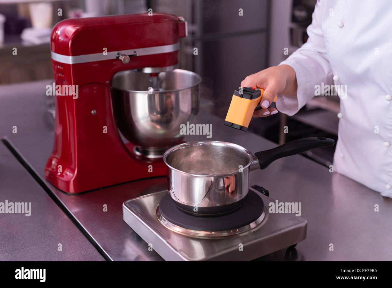 Professional baker measuring temperature of water cooking dessert - Stock Image