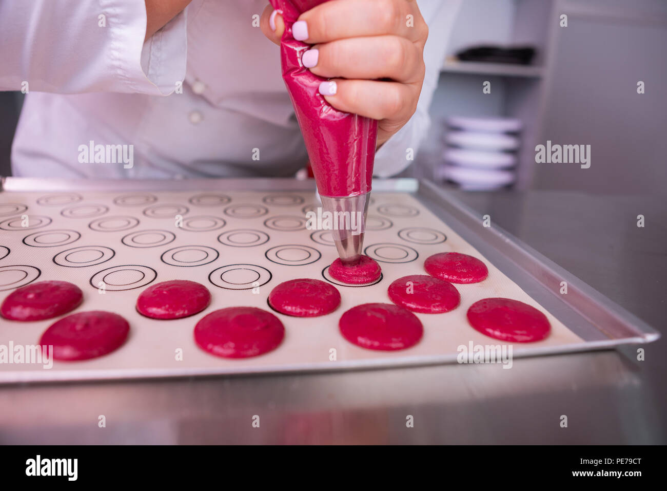 Female baker using pastry bag while cooking pink marshmallows - Stock Image