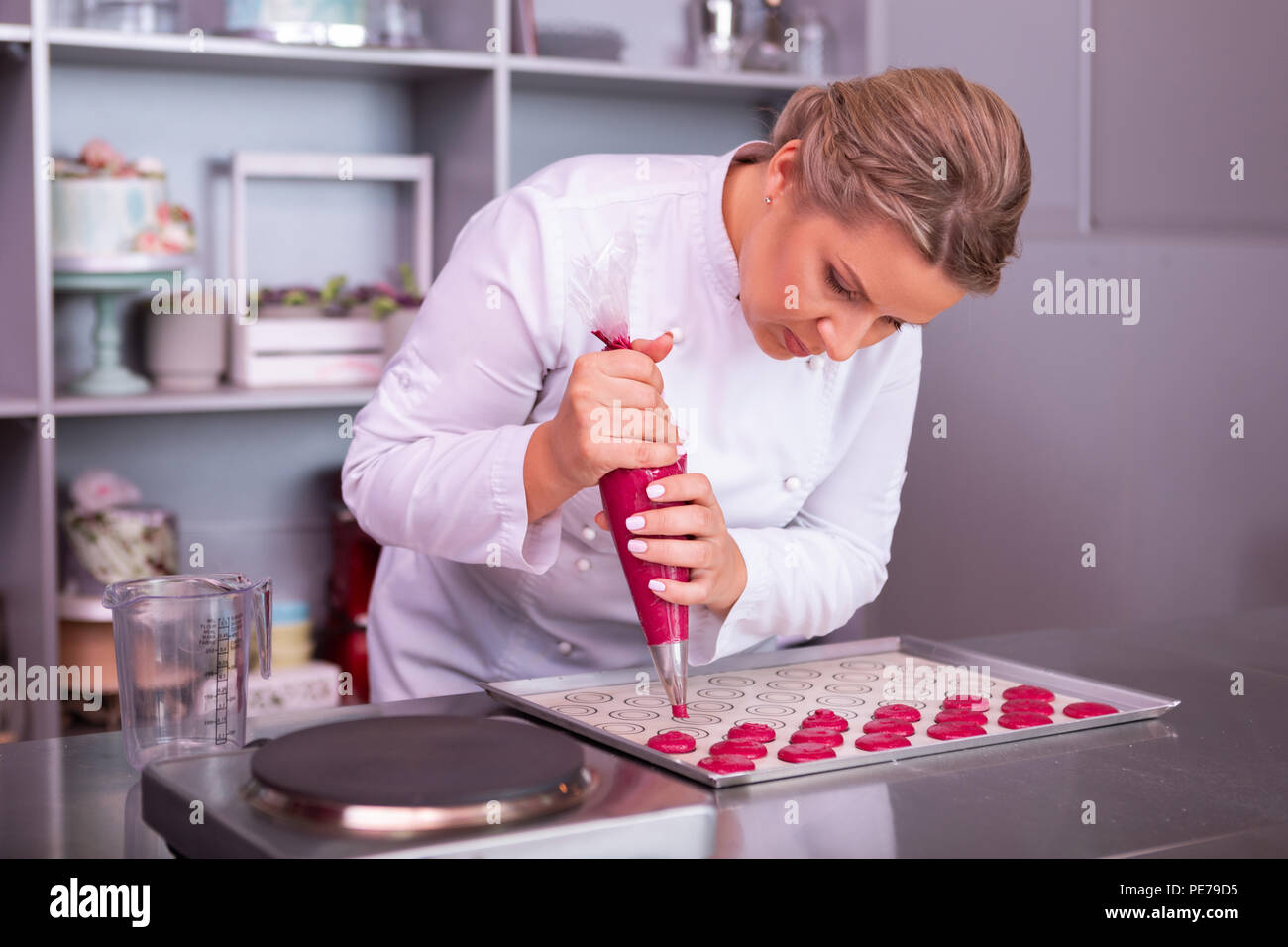 Blonde-haired baker with nice hairstyle feeling very busy Stock Photo
