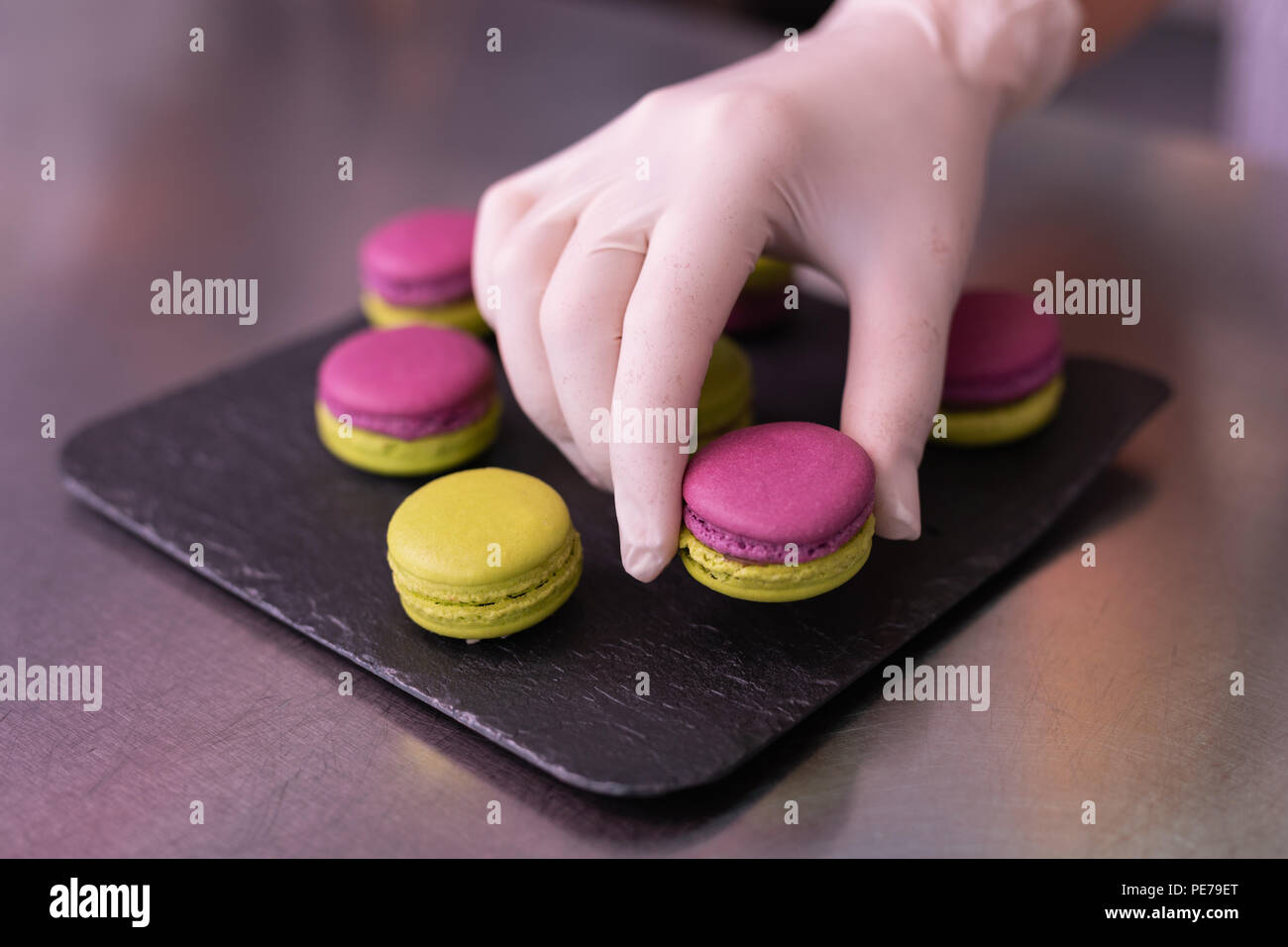 Master of confectionary putting nice macaroons on black plate - Stock Image