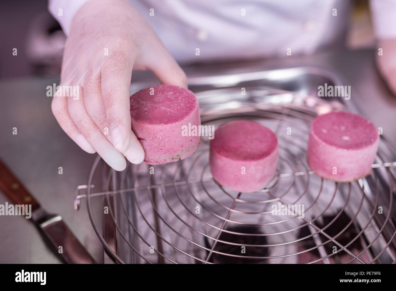 Baker taking frozen semi products for fruit cakes - Stock Image