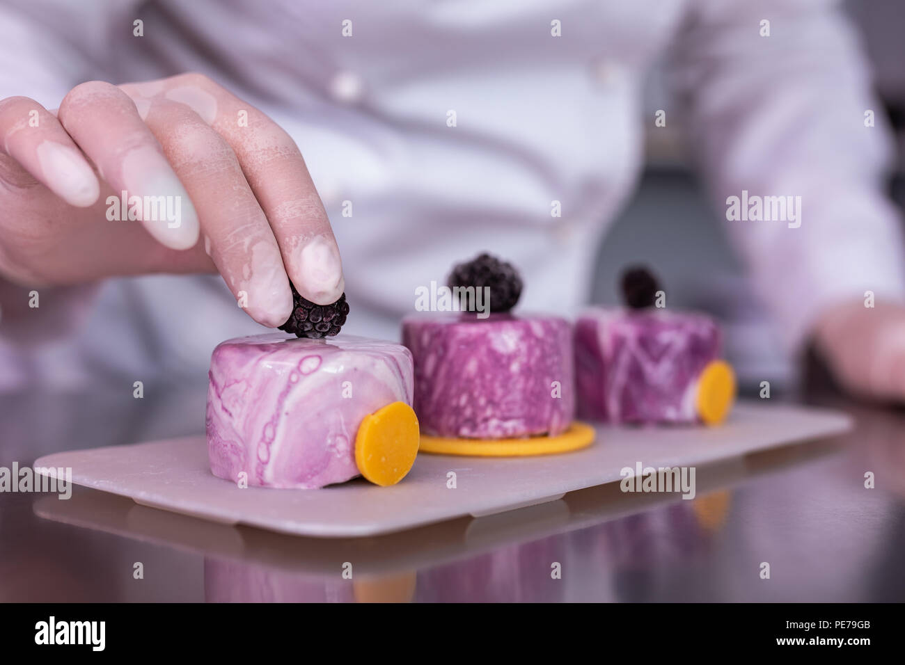 Professional confectioner giving master class on decorating desserts - Stock Image