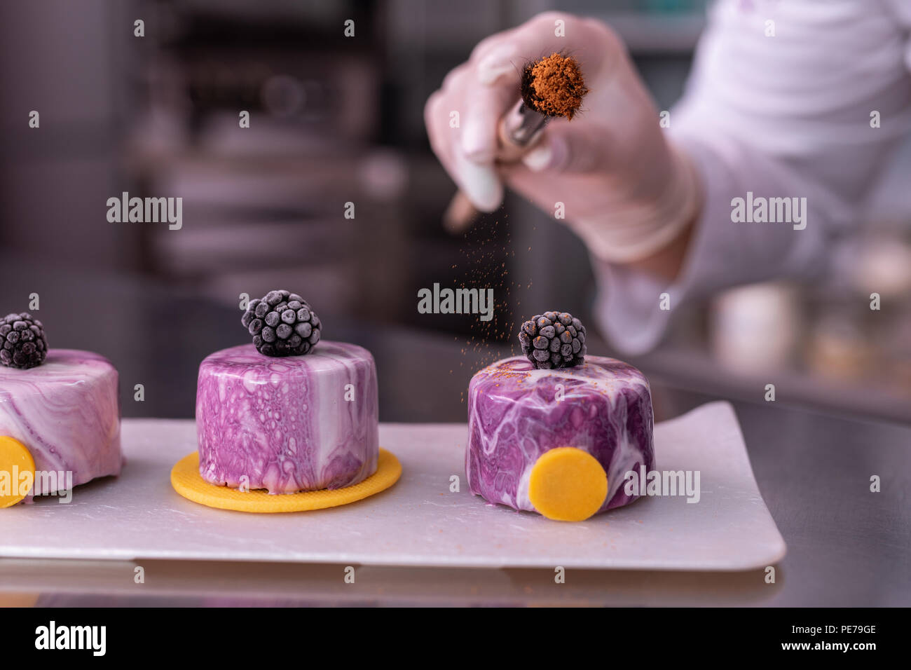 Baker sprinkling some cinnamon on cake with mirror icing - Stock Image