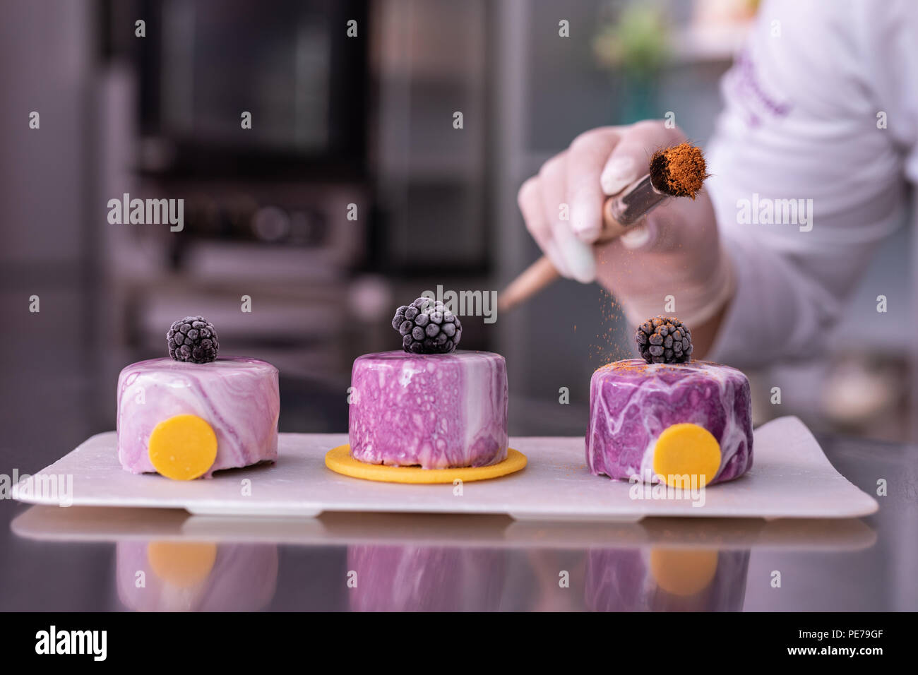 Chef decorating her cakes with cinnamon holding bakery brush - Stock Image
