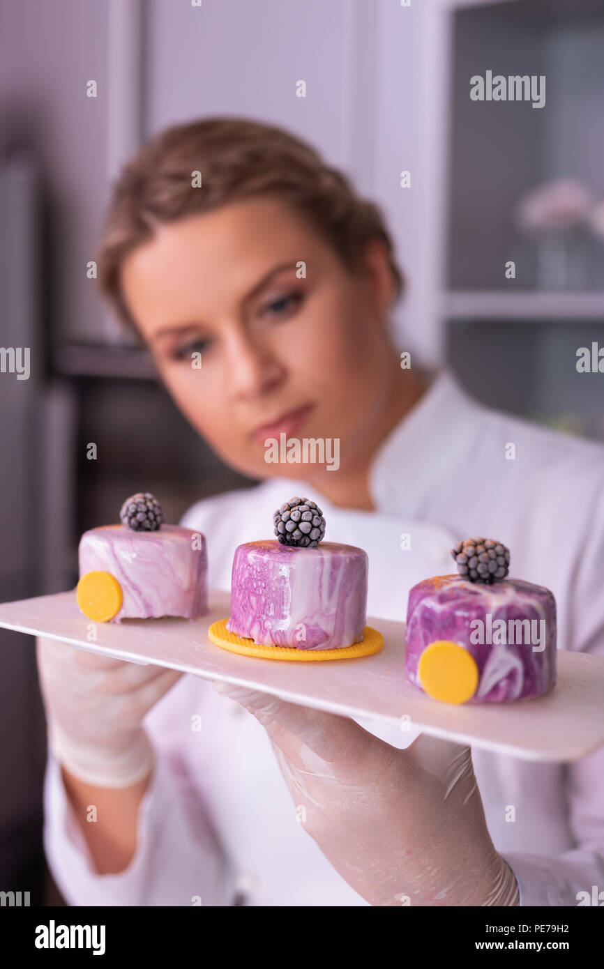 Appealing master of confectionary looking at three blueberry cakes - Stock Image