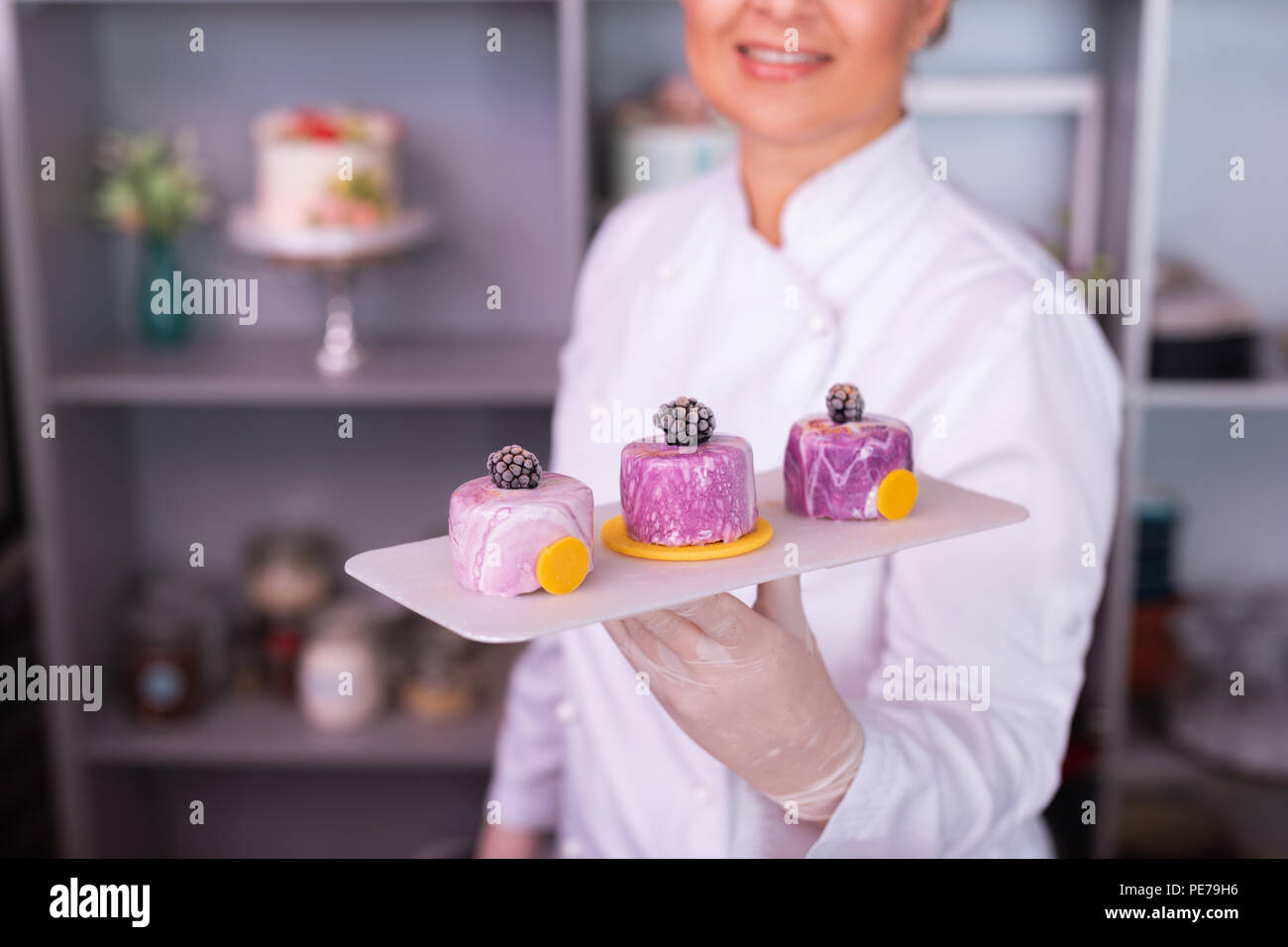 Beaming blonde-haired baker showing the result of her work - Stock Image