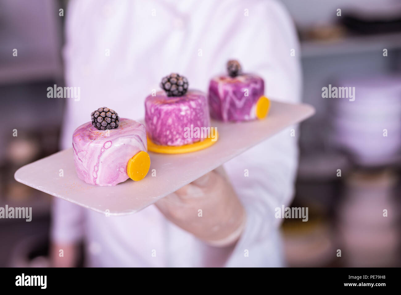 Chef wearing gloves and jacket holding plate with cakes - Stock Image