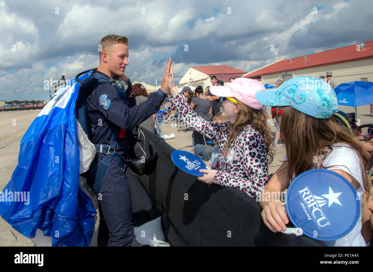 Jenna Koch (center), gives a high five to Cadet 1st Class Garrett Nobley, U.S. Air Force Academy Wings of Blue team member, during the 2015 Joint Base San Antonio Air Show and Open House Nov. 1, 2015, at JBSA-Randolph, Texas. Air shows allow the Air Force to display the capabilities of our aircraft to the American taxpayer through aerial demonstrations and static displays and allowing attendees to get up close and personal to see some of the equipment and aircraft used by the U.S. military today. (U.S. Air Force photo by Johnny Saldivar) Stock Photo