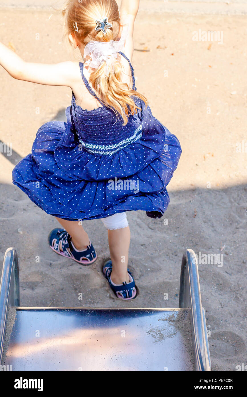 Cute little girl having fun on slide at a playground outdoors in summer. - Stock Image