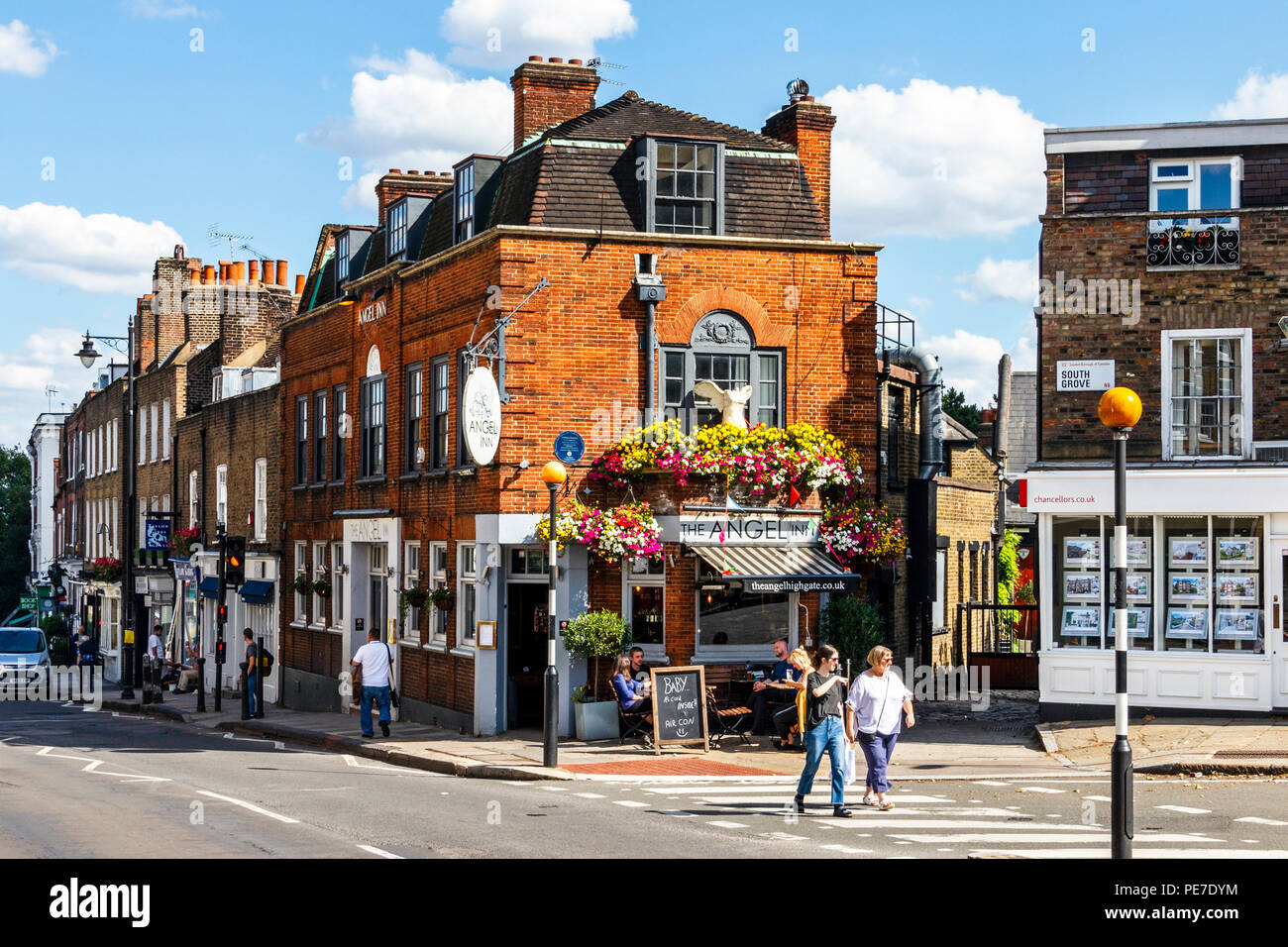Customers drinking outside the historic Angel Inn in Highgate Village, London, UK during a heatwave Stock Photo