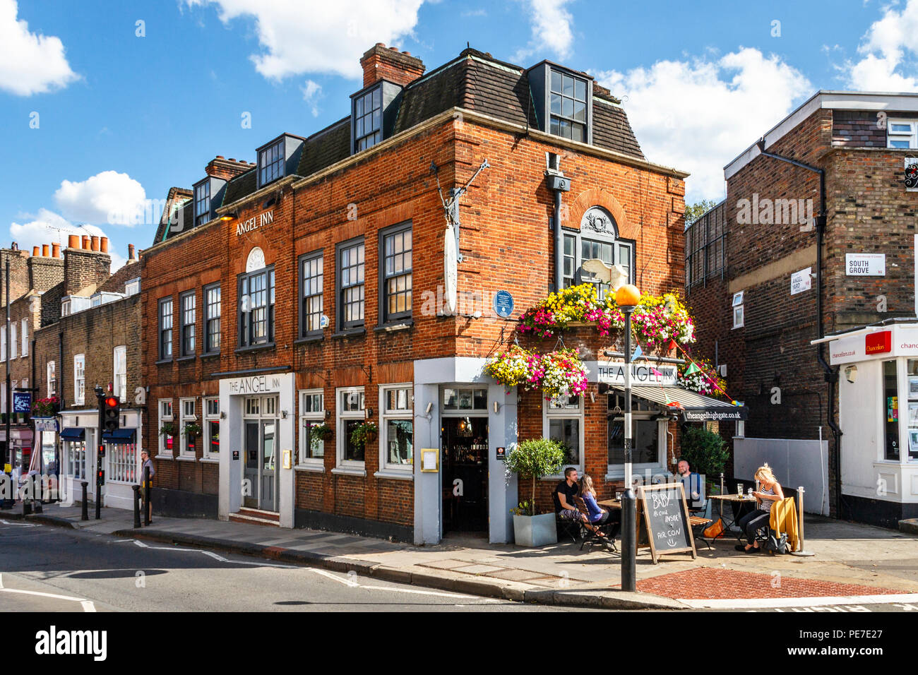 Customers drinking outside the historic Angel Inn in Highgate Village, London, UK during a heatwave - Stock Image