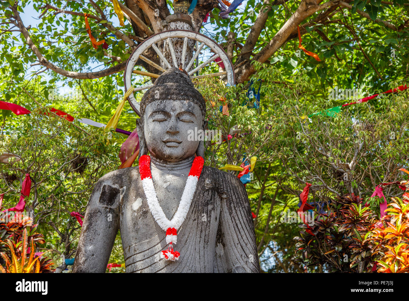 Stone statue of Sitting Buddha under the tree, with a garland in red and white colors of Indonesian flag for Indonesia Independence Day, Bali, Indones Stock Photo