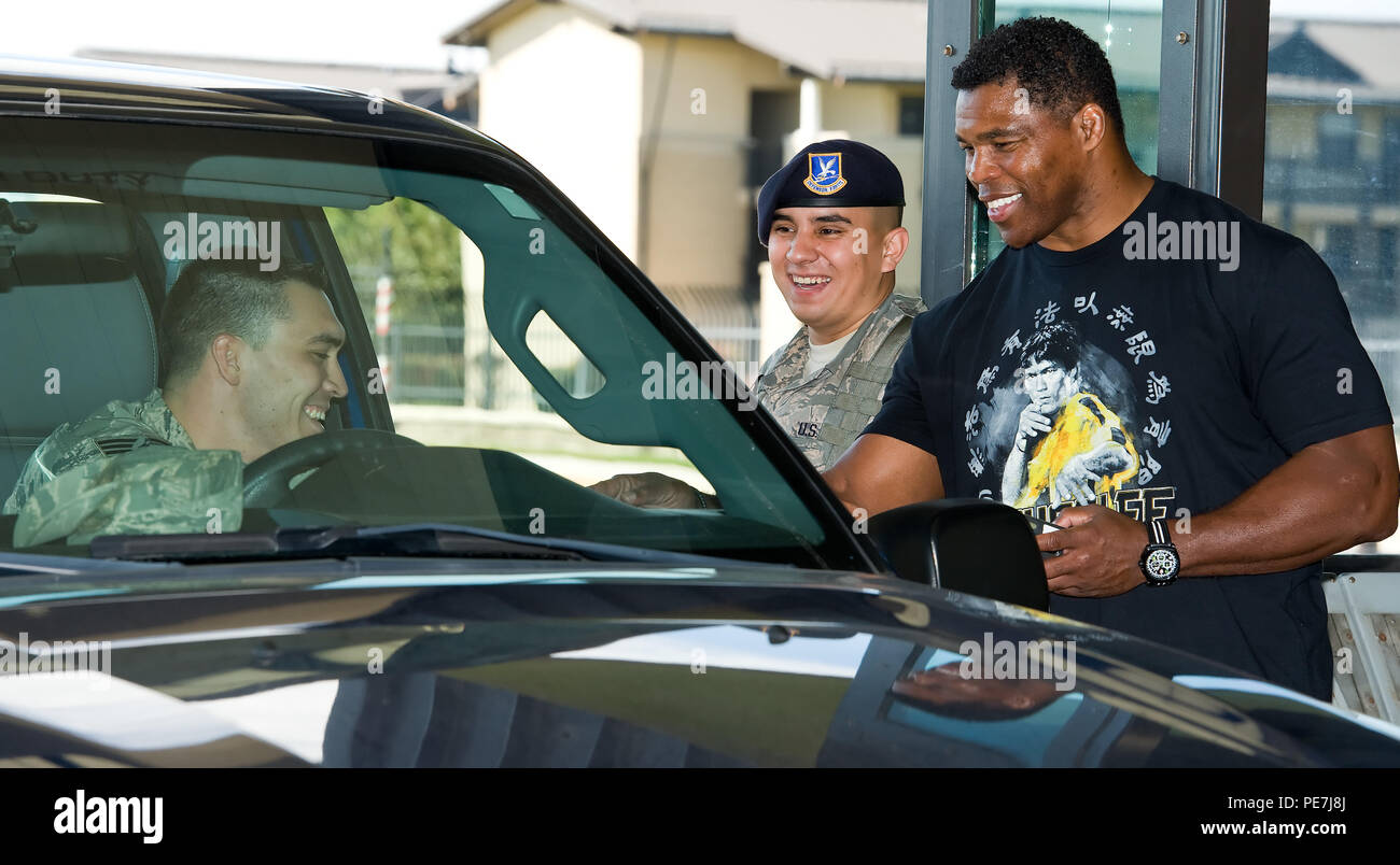 Herschel Walker, right, checks a Team Dover member's identification card, along with Airman 1st Class Eric Martinez, 436th Security Forces Squadron response force member, middle, at the main gate Oct. 13, 2015, on Dover Air Force Base, Del. Walker met with 436th SFS personnel, toured the Commercial Vehicle Inspection Facility, checked identification cards and met with a military working dog team during his three-day visit to Dover Air Force Base. (U.S. Air Force photo/Roland Balik) - Stock Image