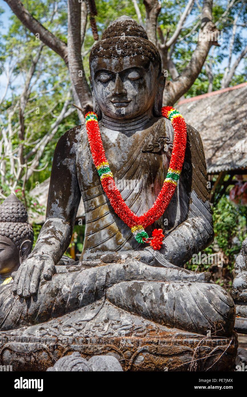 Stone statue of Sitting Buddha under the tree, Bali, Indonesia. Vertical image. Stock Photo