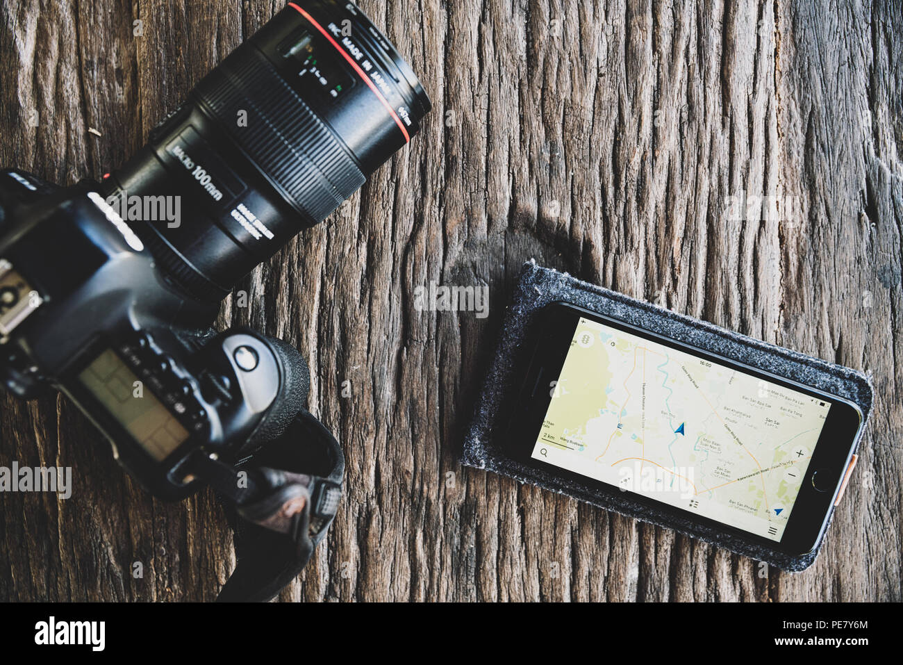 Top view identity photo equipment traveller tourist on wooden table, dslr camera and smartphone with map for planning route trip - Stock Image
