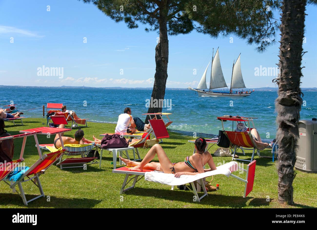 Tourists at the shore of a hotel, Bardolino, province Verona, Garda lake, Lombardy, Italy Stock Photo