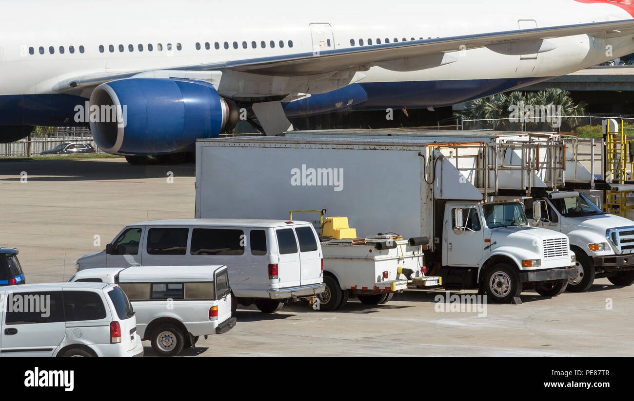 Passenger jet airside with catering and cleaning trucks - Stock Image