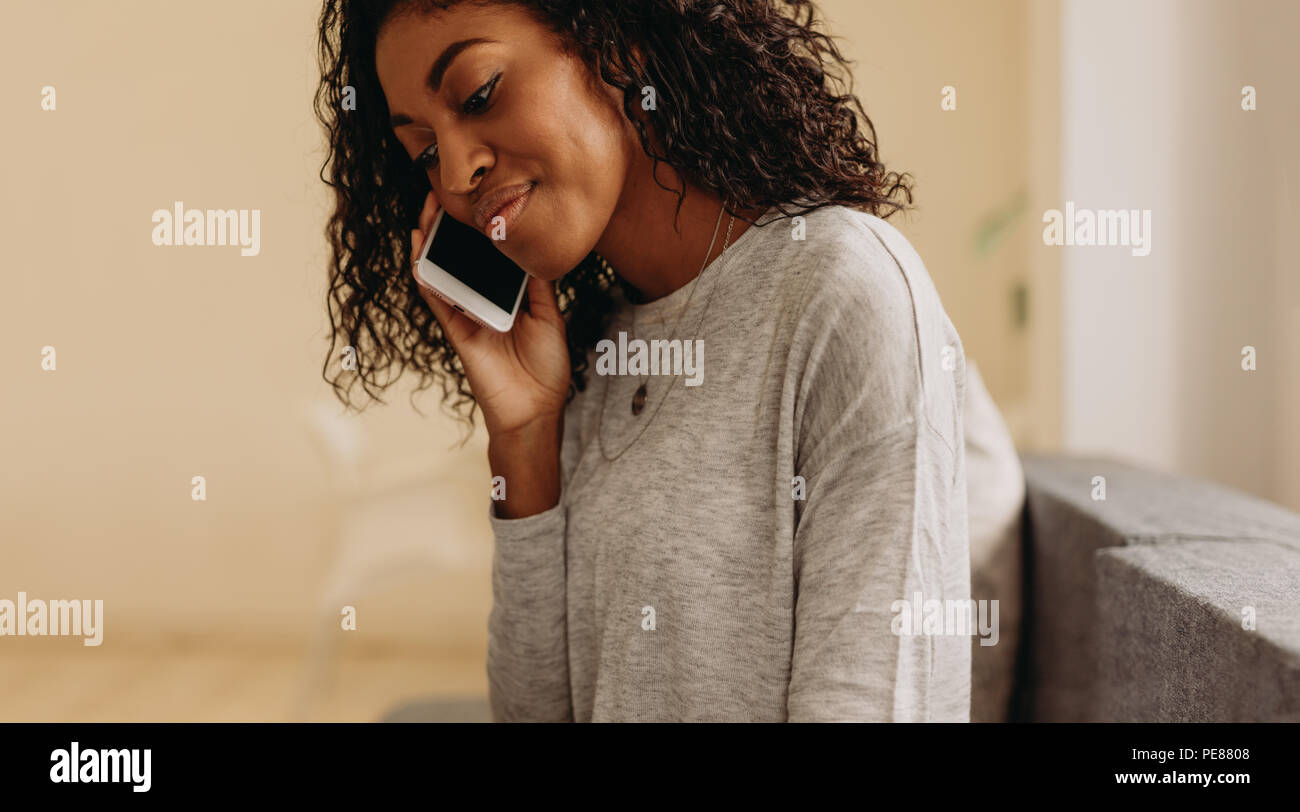 Close up of curly haired woman talking over mobile phone. Woman talking over mobile phone sitting at home. - Stock Image