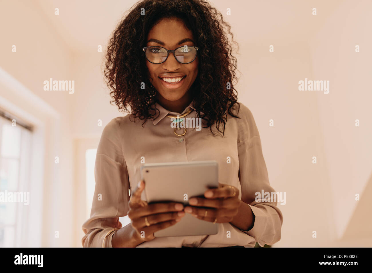 Portrait of a businesswoman in formal attire holding a tablet pc in hands. Curly haired woman entrepreneur in spectacles at home with a tablet pc in h - Stock Image