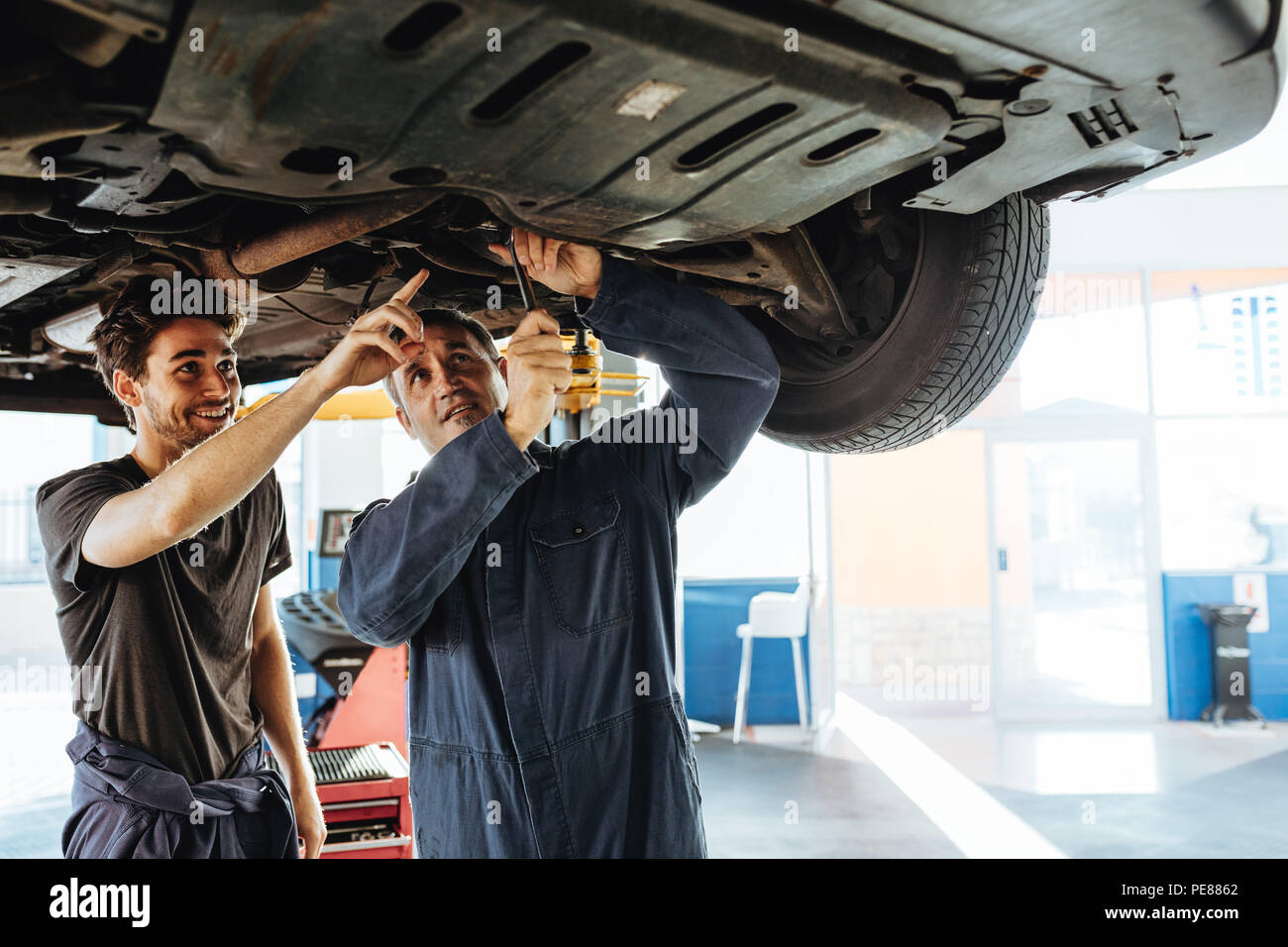 Mechanic fixing the car with coworker pointing and smiling. Two auto repair men working under a lifted vehicle in garage. - Stock Image
