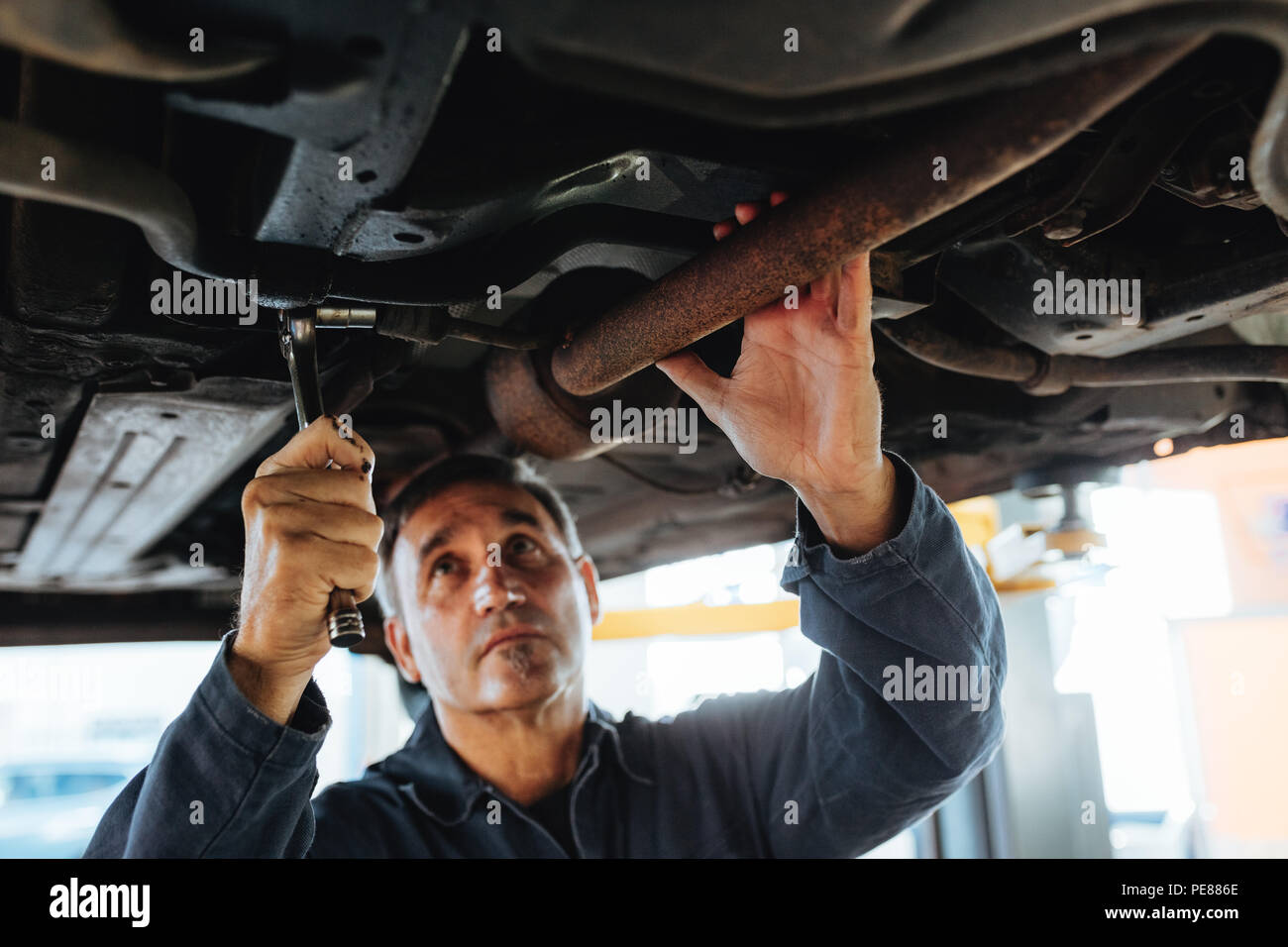 Man tightening a silencer pipe with wrench spanner in auto garage. Mechanic working under a lifted car in repair shop. - Stock Image