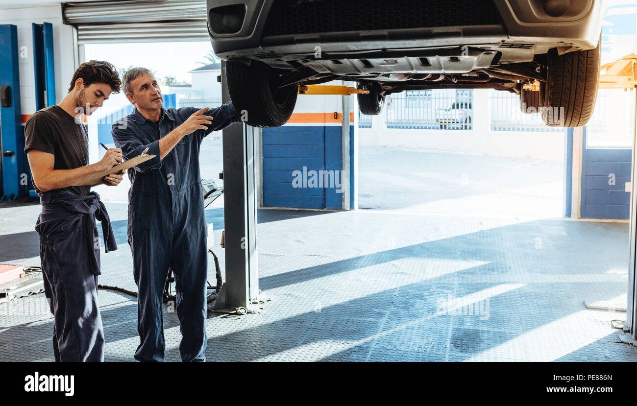 Two car mechanics in uniform examining the car and making notes for the repairs to be done. Mechanic making list of car malfunctions. - Stock Image