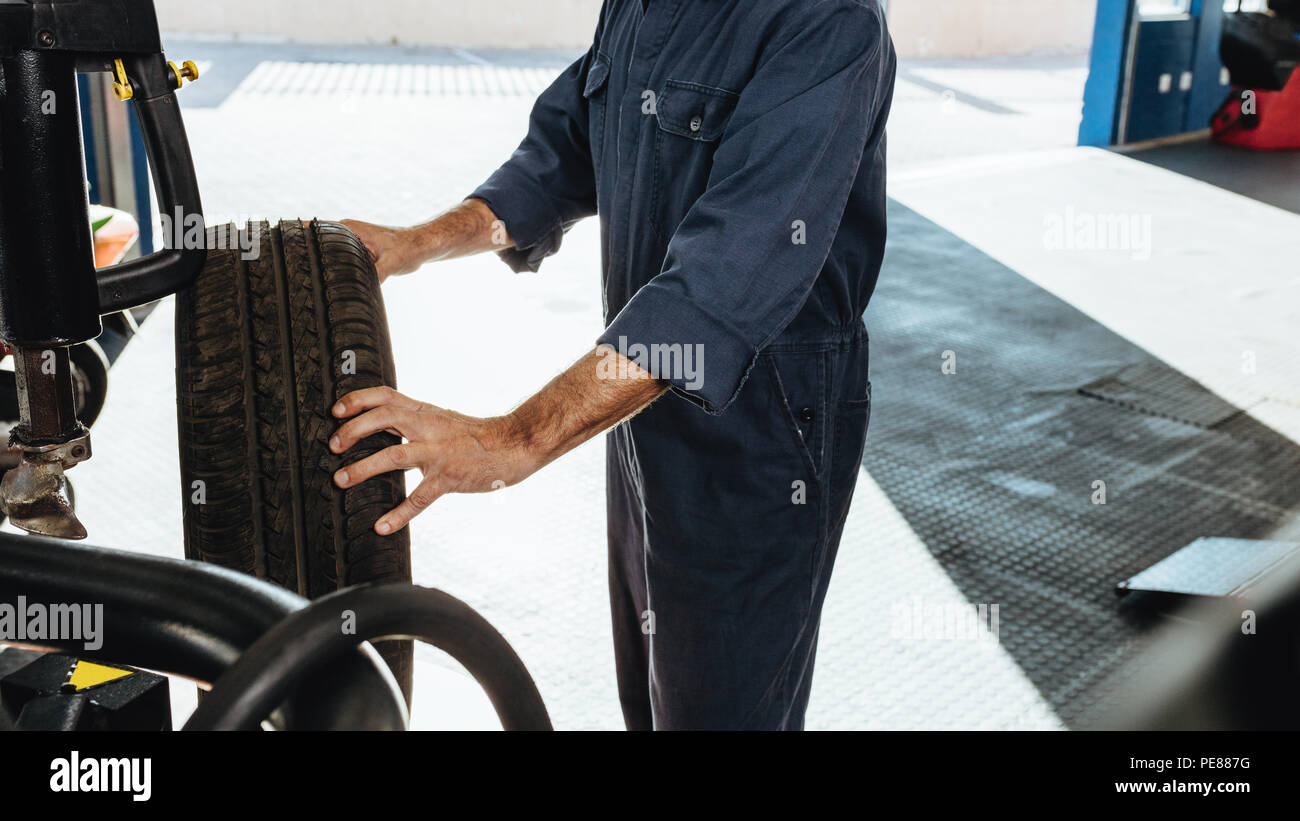 Cropped shot of a mechanic doing car tire checkup on machine in service station. Man inspecting the tire grip in workshop. - Stock Image
