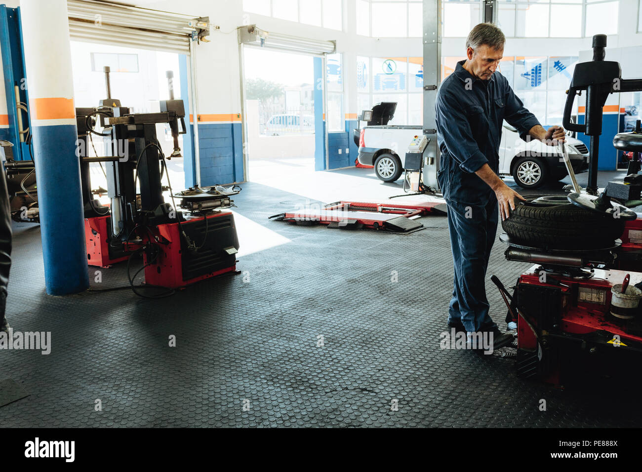 Car service station with mechanic removing tire from disc. Technician working on car tire removing machine in workshop. - Stock Image