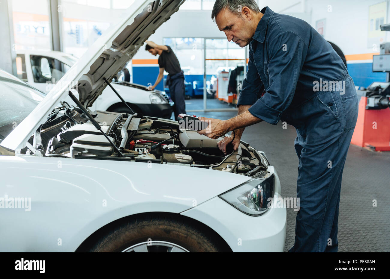 Car mechanic with diagnostic device for reading the error codes. Mechanic checking the car in service station. Stock Photo