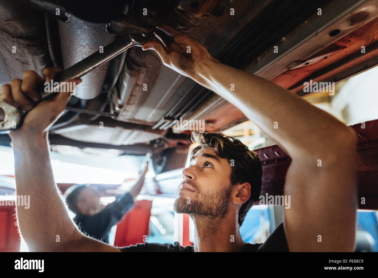 Young man working underneath a lifted car. Mechanic tightening a car part with spanner in automobile service center. - Stock Image