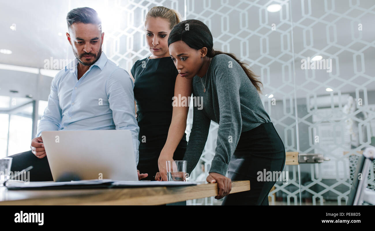 Three diverse business people talking together over a laptop while working at a table in office boardroom. Business team working on their business pro - Stock Image