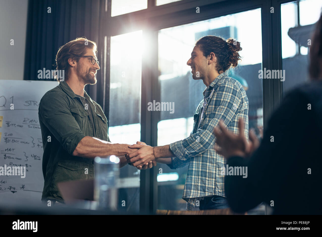 Two business people shaking hands after a successful meeting. Businessman congratulating and appreciating the performance of a colleague in meeting ro - Stock Image