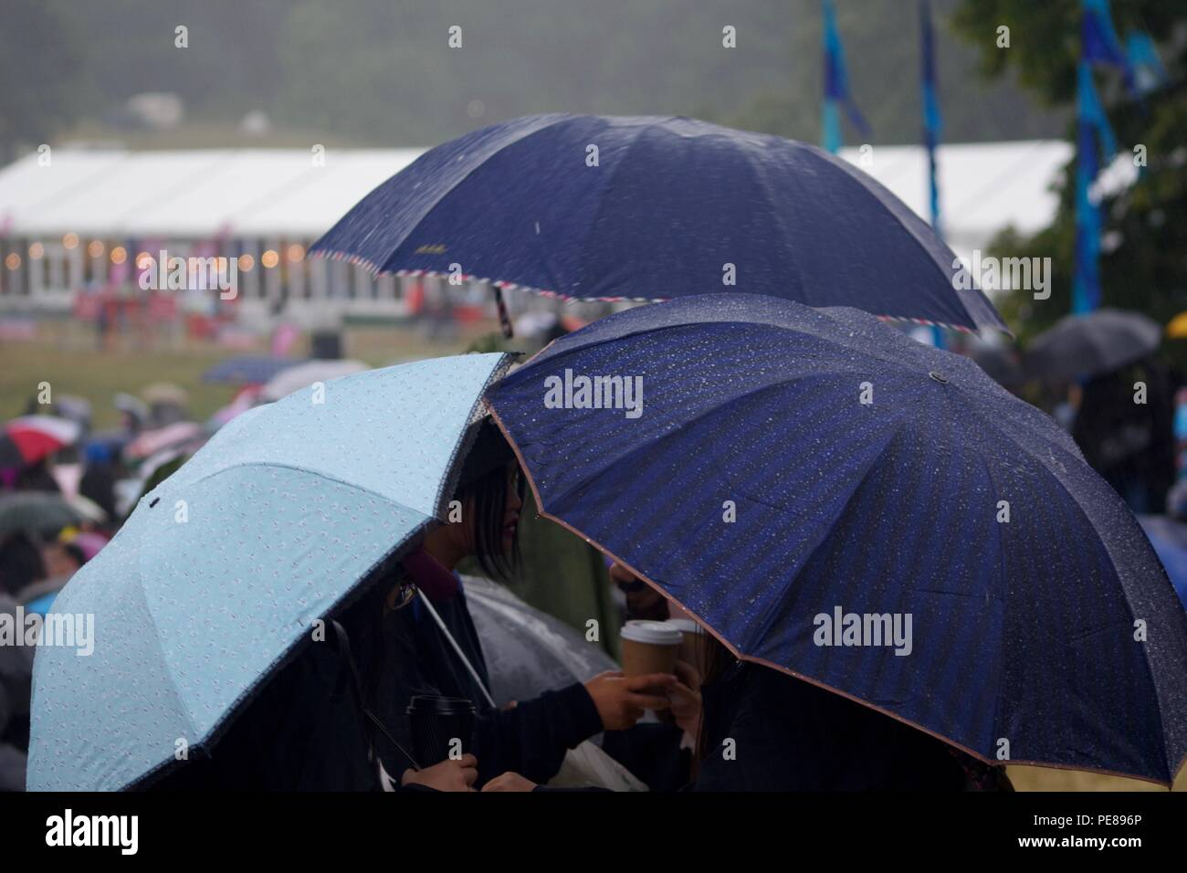 Trio of Blue Umbrella's Sheltering a Huddle of Friends at Bristol Balloon Fiesta on a Rainy Summer's Day. UK. 2018. - Stock Image
