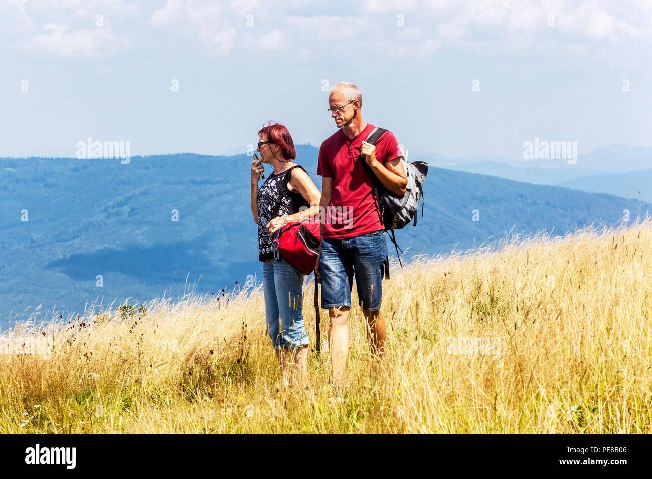 Active aging, Seniors hiking on a mountain meadow, Bile Karpaty Mountains, White Carpathians, Czech Slovakian border, Czech Republic, Slovakia - Stock Image