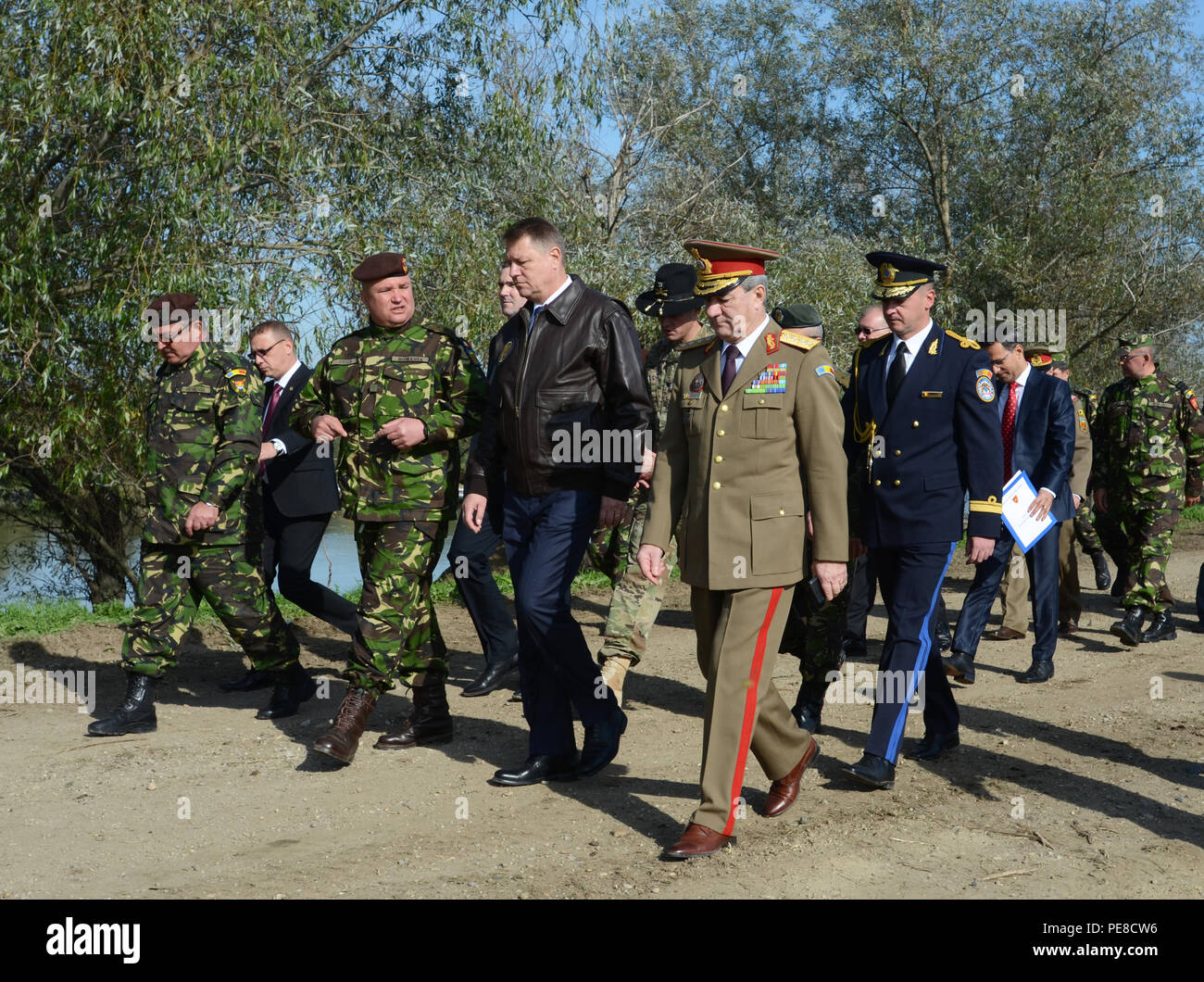 The President of Romania, Klaus Iohannis (right center), walks and talks with Lt. Gen. Nicolae-Ionel Ciuca, the chief of the Romanian Army, on the upper bank of the Mures River, near Arad, Romania during Exercise Dragoon Crossing, Oct. 24-26, 2015. Exercise Dragoon Crossing – Romania is a strengthening of NATO's persistent presence in the region in support of Operation Atlantic Resolve. (U.S. Army photo by Staff Sgt. Steven M. Colvin/10th Press Camp Headquarters) - Stock Image