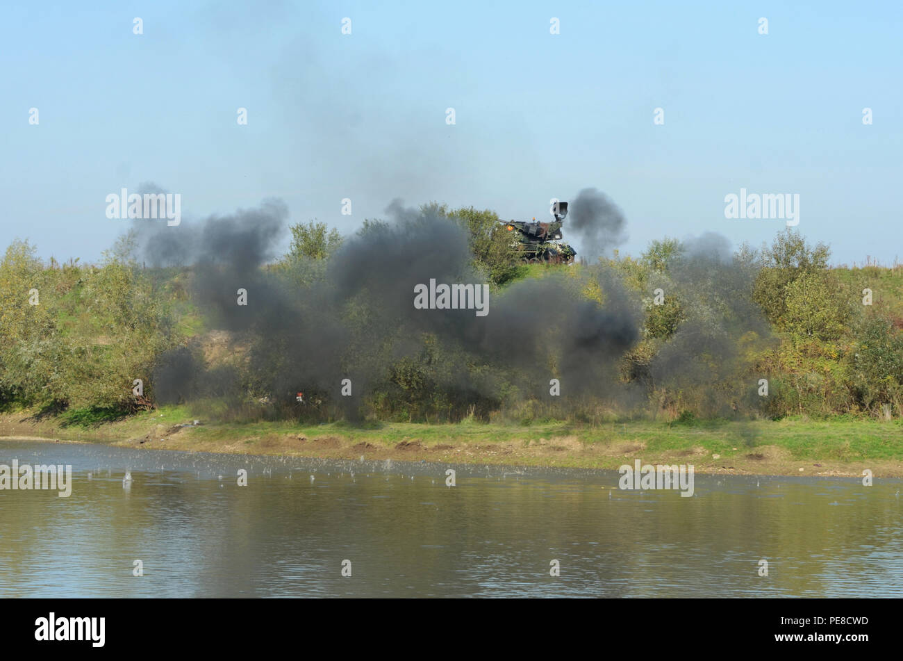 Debris splashes into the Mures River as smoke rises from the bank from a simulated airstrike explosion during Exercise Dragoon Crossing – Romania, near Arad, Romania, Oct. 24-26, 2015.  Dragoon Crossing – Romania is a strengthening of NATO's persistent presence in the region in support of Operation Atlantic Resolve. (U.S. Army photo by Staff Sgt. Steven M. Colvin/10th Press Camp Headquarters) - Stock Image
