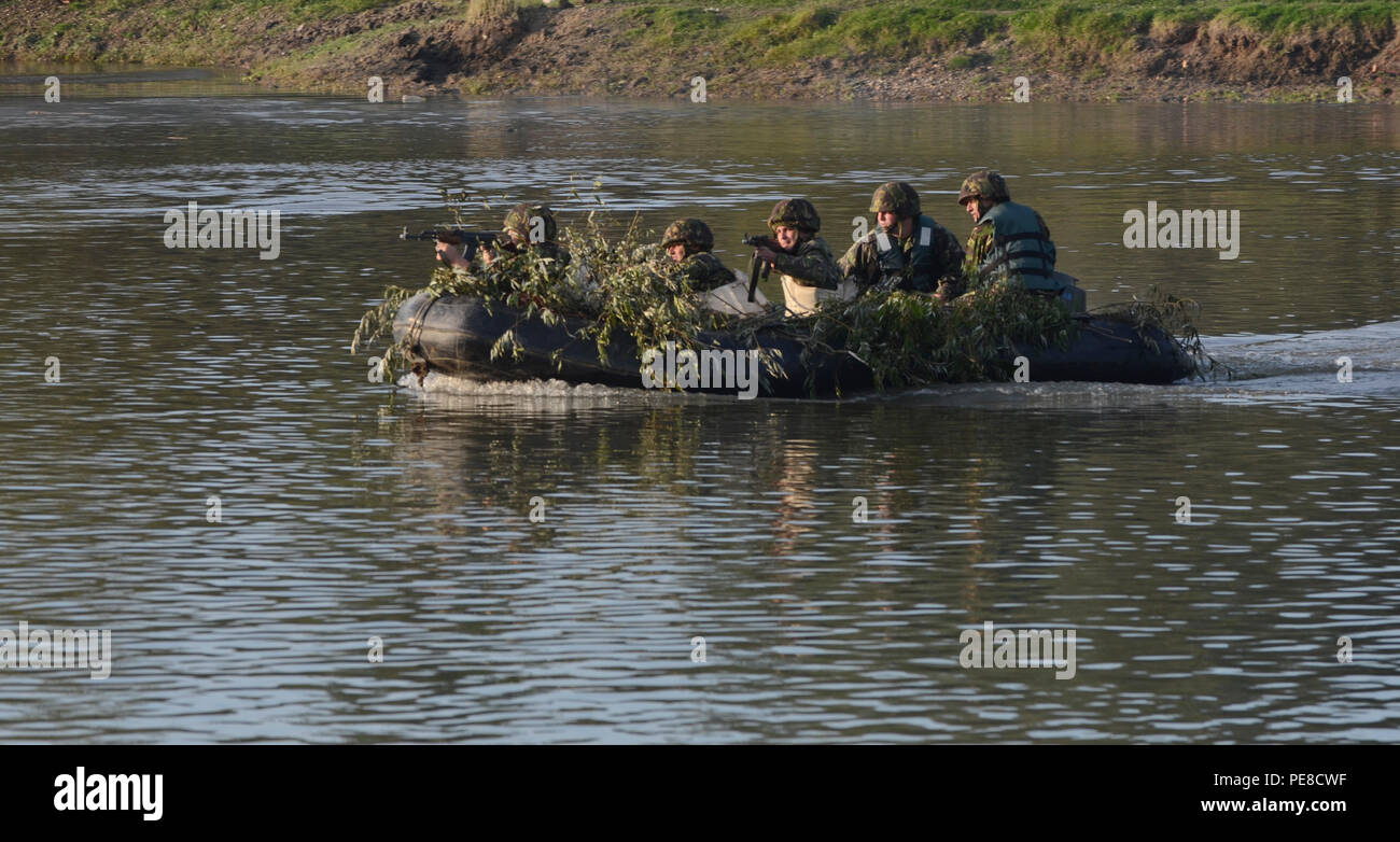 Romanian Soldiers ride across the Mures River as they suppress enemy fire during Exercise Dragoon Crossing – Romania, near, Arad, Romania, Oct. 24-26, 2015. Exercise Dragoon Crossing – Romania is a strengthening of NATO's persistent presence in the region in support of Operation Atlantic Resolve. (U.S. Army photo by Staff Sgt. Steven M. Colvin/10th Press Camp Headquarters) - Stock Image