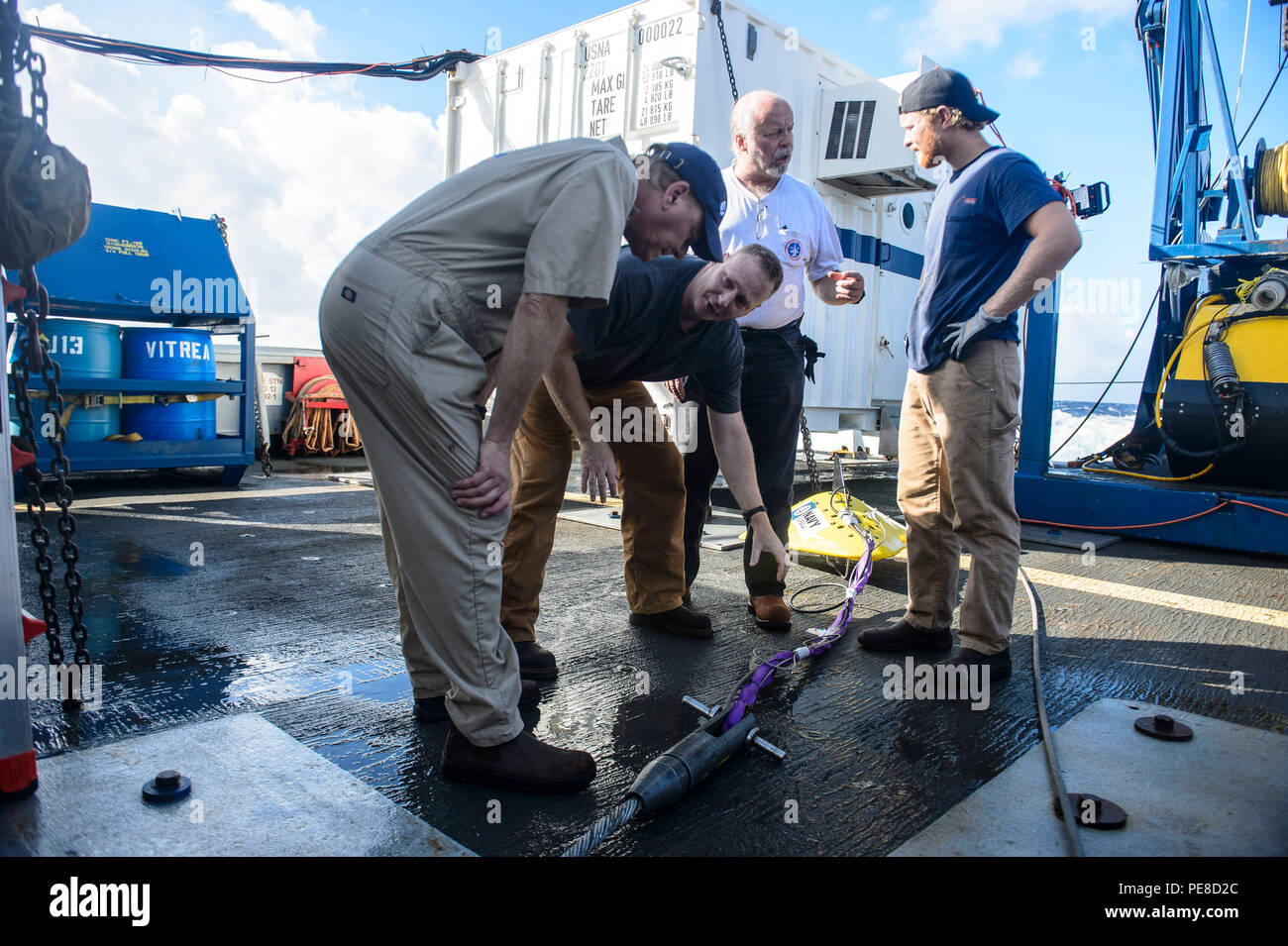 151023-N-RZ218-069   BAHAMAS (Oct. 23, 2015) Contractors with Phoenix International Incorporated prepares a tow pinger locater 25 (TPL 25) for the upcoming salvage mission aboard USNS Apache (T-ATF 172). USNS Apache departed Norfolk, Va., Oct. 19, to begin searching for wreckage from the missing U.S. Flagged merchant vessel El Faro. The ship is equipped with several pieces of underwater search equipment, including a voyage data recorder locator, side-scan sonar and an underwater remote operated vehicle. The Navy's mission will be to first locate the ship and, if possible, to retrieve the voyag - Stock Image